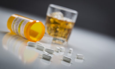 Several Prescription Drugs Spilled From Fallen Bottle Near Glass of Alcohol.