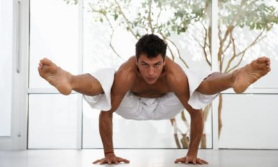 Man in yoga position balancing body off floor, portrait