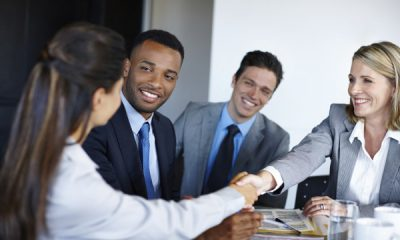 Shot of professional coworkers shaking hands during a meeting in the office