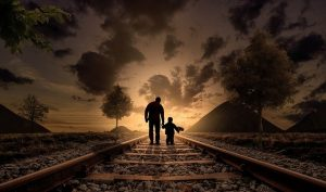 A father and son walking along railway
