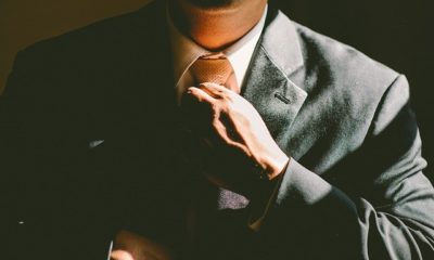 A businessman putting on a tie.