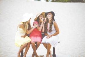 Three pretty girls sitting on a bench and chatting. They are wearing big summer hats.