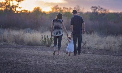 Parents walking their daughter in the countryside.