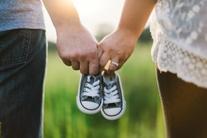 Mommy and daddy holding hands and little baby shoes.