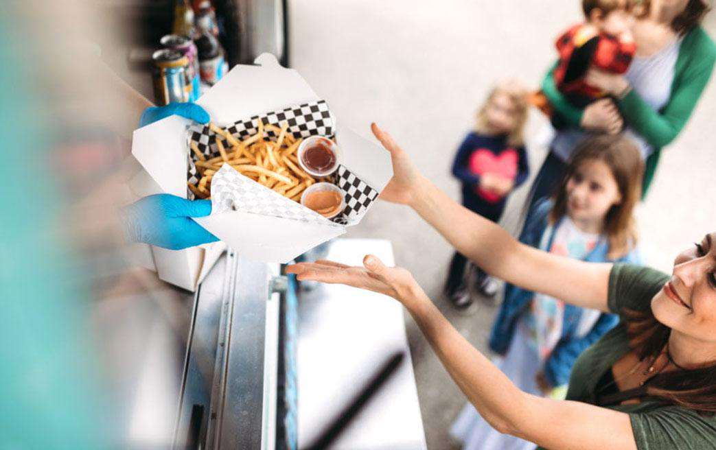 Woman buying fries from a food truck with kids in the background